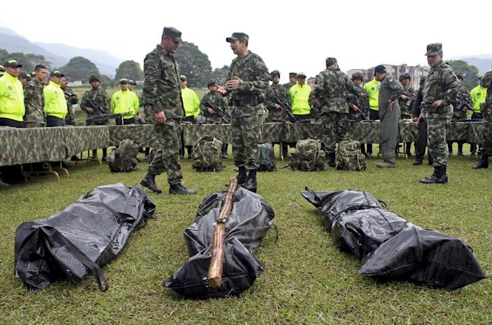 Colombian police soldiers stand by the bodies of Revolutionary Armed Forces of Colombia (FARC) rebels killed in combat, in January 2014, at a military airport in Ibague, department of Tolima (AFP Photo/Felipe Caicedo)