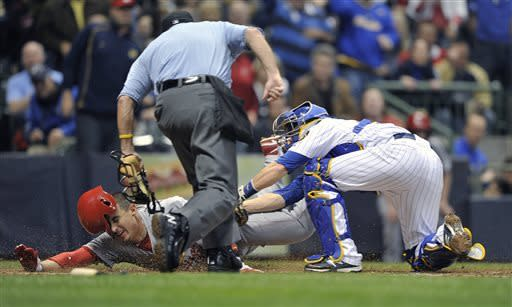St. Louis Cardinals' Allen Craig is tagged out at home by Milwaukee Brewers' Jonathan Lucroy while trying to score on a ball hit Yadier Molina, as home plate umpire Dale Scott watches during the third inning of a baseball game Friday, May 3, 2013, in Milwaukee. (AP Photo/Jim Prisching)