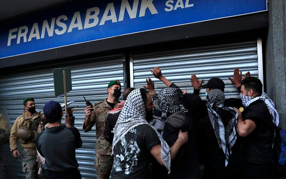 A Lebanese army officer, center, pushes back protesters who were trying to break a bank door, during a protest demanding that local banks allow them to withdraw their money - Hussein Malla/AP