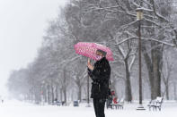 Paulina Lozano speaks with her parents by phone, as snow falls on the National Mall, Sunday, Jan. 31, 2021, in Washington. (AP Photo/Alex Brandon)
