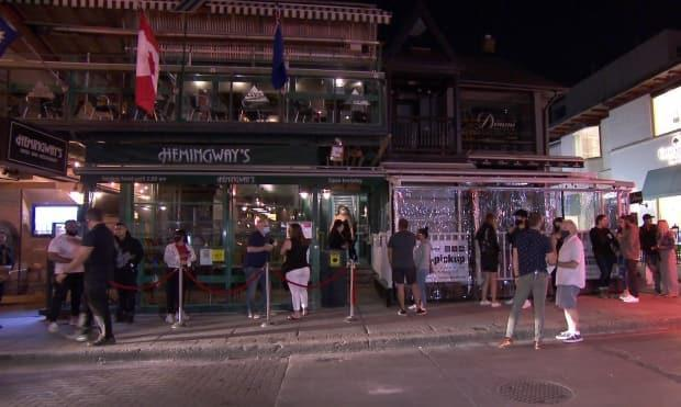 Patrons were lined up outside this Toronto restaurant in advance of 12:01 a.m. Friday, when most of the province moved into the first phase of reopening. It's multiple outdoor patios were at limited capacity until 2 a.m.