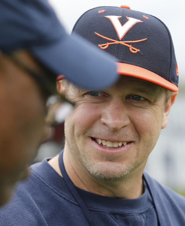 FILE - In this April 6, 2017, file photo, Virginia football coach Bronco Mendenhall talks to a fellow coach after spring football practice at their indoor facility in Charlottesville, Va. (AP Photo/Steve Helber, File)