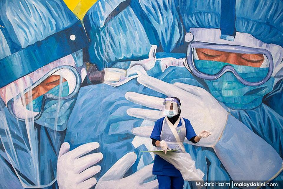 A doctor wearing personal protective equipment waits for patients at a drive-thru Covid-19 testing centre outside Clinic Ajwa in Shah Alam, Selangor on Dec 10, 2020.