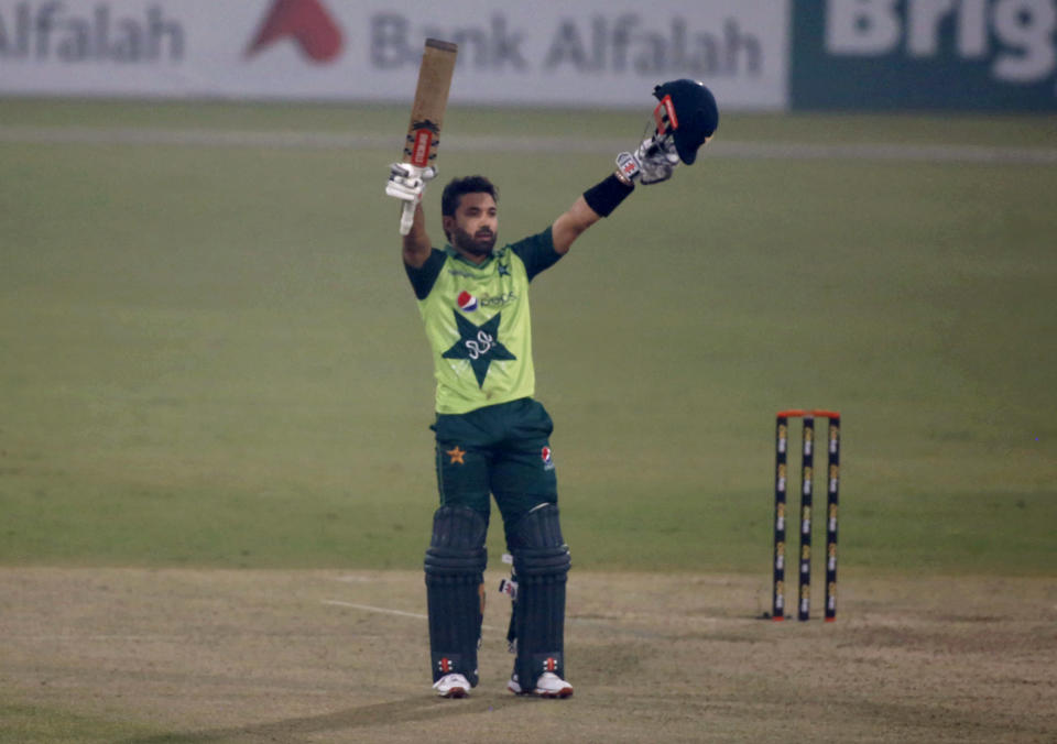 Pakistan's Mohammad Rizwan raises bat and helmet to celebrate his century during the 1st Twenty20 cricket match between Pakistan and South Africa at the Gaddafi Stadium, in Lahore, Pakistan, Thursday, Feb. 11, 2021. (AP Photo/K.M. Chaudary)
