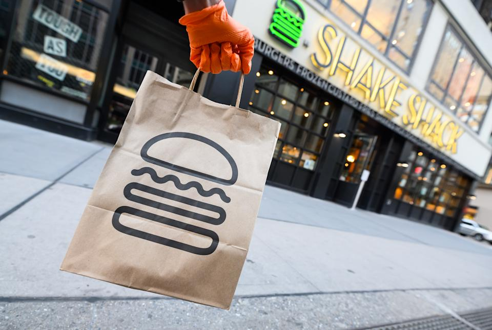 NEW YORK, NEW YORK - APRIL 22: A person wearing a protective glove holds a bag outside Shake Shack during the coronavirus pandemic on April 20, 2020 in New York City. COVID-19 has spread to most countries around the world, claiming over 184,000 lives lost with over 2.6 million infections reported. (Photo by Noam Galai/Getty Images)
