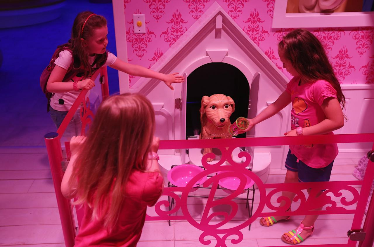 BERLIN, GERMANY - MAY 16:  Lara (L), Josi and Luna, all 6, pet a plastic dog that emerged from his doghouse at the Barbie Dreamhouse Experience on May 16, 2013 in Berlin, Germany. The Barbie Dreamhouse is a life-sized house full of Barbie fashion, furniture and accessories and will be open to the public until August 25 before it moves on to other cities in Europe.  (Photo by Sean Gallup/Getty Images)