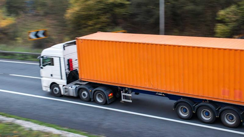 HGV lorry with orange shipping container in motion on the road