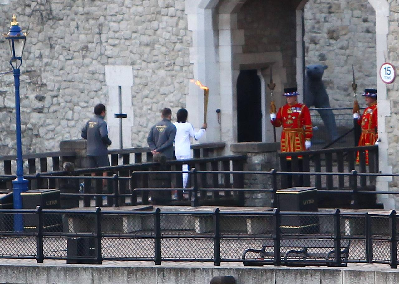 Dame Kelly Holmes holds the Olympic Flame outside the entrance to the Tower of London London, England - 20.07.12 Mandatory Credit: WENN.com
