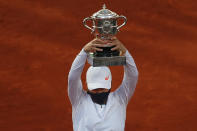 Poland's Iga Swiatek holds the trophy after winning the final match of the French Open tennis tournament against Sofia Kenin of the U.S. in two sets 6-4, 6-1, at the Roland Garros stadium in Paris, France, Saturday, Oct. 10, 2020. (AP Photo/Alessandra Tarantino)