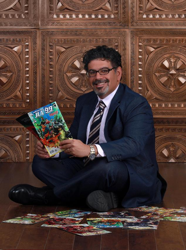 "In this image released by Teshkeel Media Group, comic book author Naif Al-Mutawa holds up copies of his comic book series ""The 99,""  on Long Island, N.Y. (AP Photo/Teshkeel Media Group, Cara Hromada Photography)"