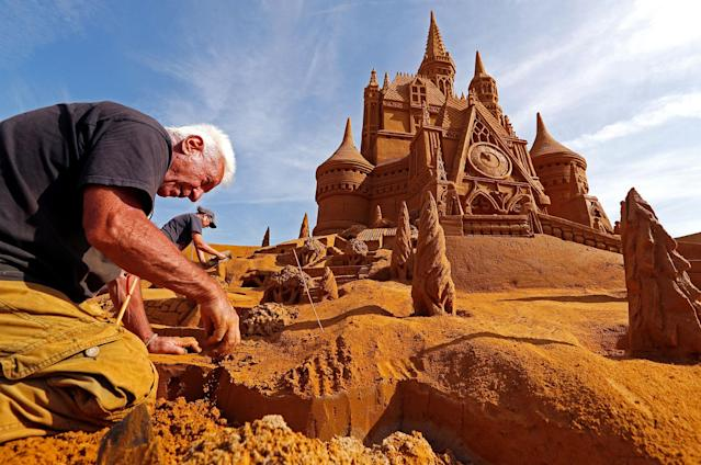 "<p>Sand carver Franco Daga from Italy works on a sculpture during the Sand Sculpture Festival ""Disney Sand Magic"" in Ostend, Belgium June 22, 2017. (Yves Herman/Reuters) </p>"