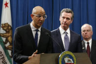 FILE - In this March 12, 2020, file photo, Dr. Mark Ghaly, secretary of the California Health and Human Services, discusses the coronavirus as Gov. Gavin Newsom, center, listens at a news conference in Sacramento, Calif. California's health department on Monday, Jan. 25, 2021, released to the public previously secret data points used to determine future hospital intensive care unit capacity, the key metric for lifting the state's coronavirus stay-at-home order. (AP Photo/Rich Pedroncelli, File)