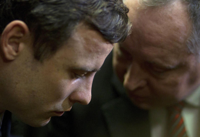 FILE In this file photo taken Monday, Aug. 19, 2013 double-amputee Olympian Oscar Pistorius, left, talks with his lawyer, Kenny Oldwage, right, at the magistrates court in Pretoria, South Africa, when Pistorius was indicted on charges of murder and illegal possession of ammunition for the shooting death of his girlfriend on Valentine's Day. Oscar Pistorius' lawyers are working with a team of American forensic specialists to help prepare the double-amputee Olympian's defense, and likely counter any evidence given by the nearly 50 police officers and criminal experts that prosecutors could call at his murder trial early next year. The U.S. forensic team is now in South Africa, Pistorius' spokeswoman told The Associated Press on Tuesday, Oct. 1, 2013, although she could not give any details of their identities or areas of expertise, or if they would stay for the trial, which begins in March and has been scheduled to last just over two weeks. (AP Photo/Themba Hadebe, File)