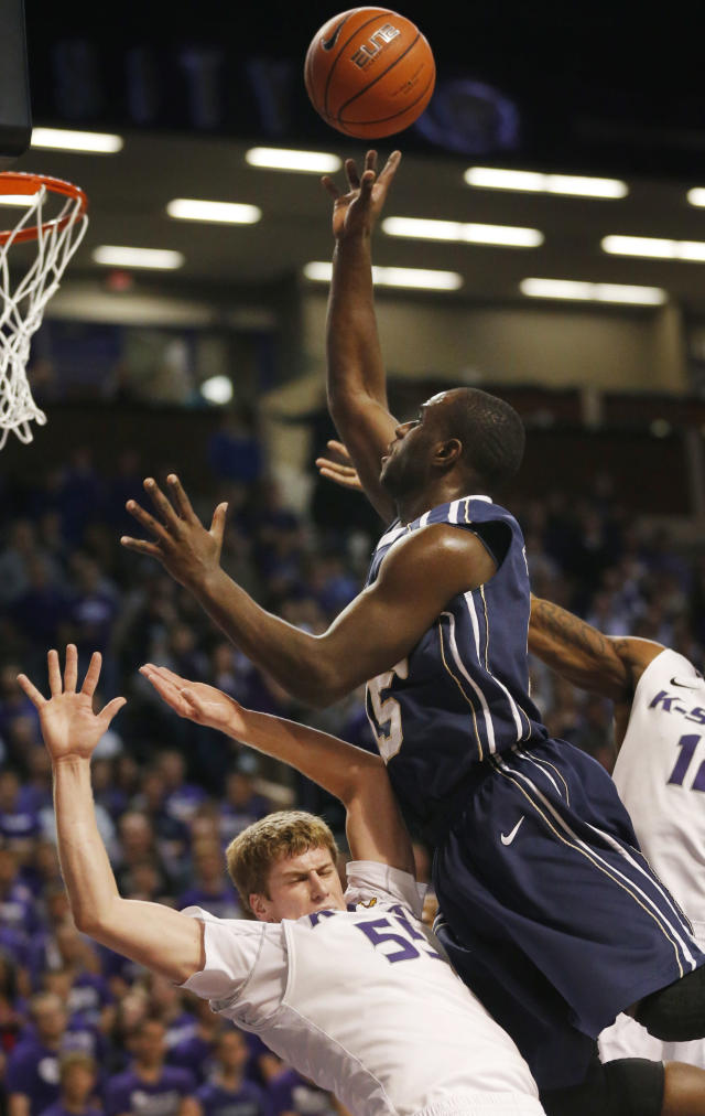 Oral Roberts guard Obi Emegano, left, charges into Kansas State guard Will Spradling (55) during the first half of an NCAA college basketball game in Manhattan, Kan., Wednesday, Nov. 13, 2013. (AP Photo/Orlin Wagner)