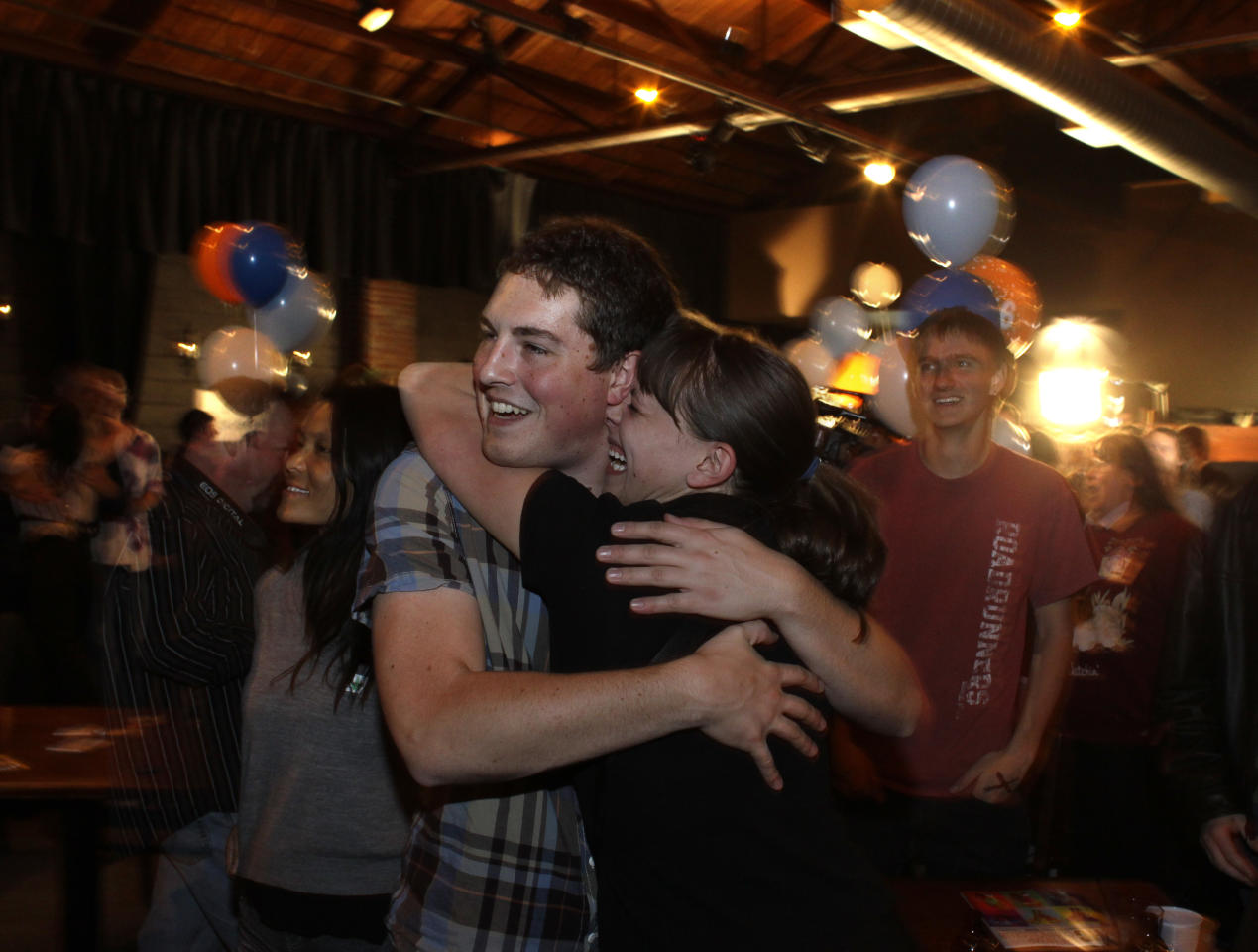 People attending an Amendment 64 watch party in a bar hug after a local television station announced the marijuana amendment's passage, in Denver, Colo., Tuesday, Nov. 6, 2012. The amendment would make it legal in Colorado for individuals to possess and for businesses to sell marijuana for recreational use. (AP Photo/Brennan Linsley)