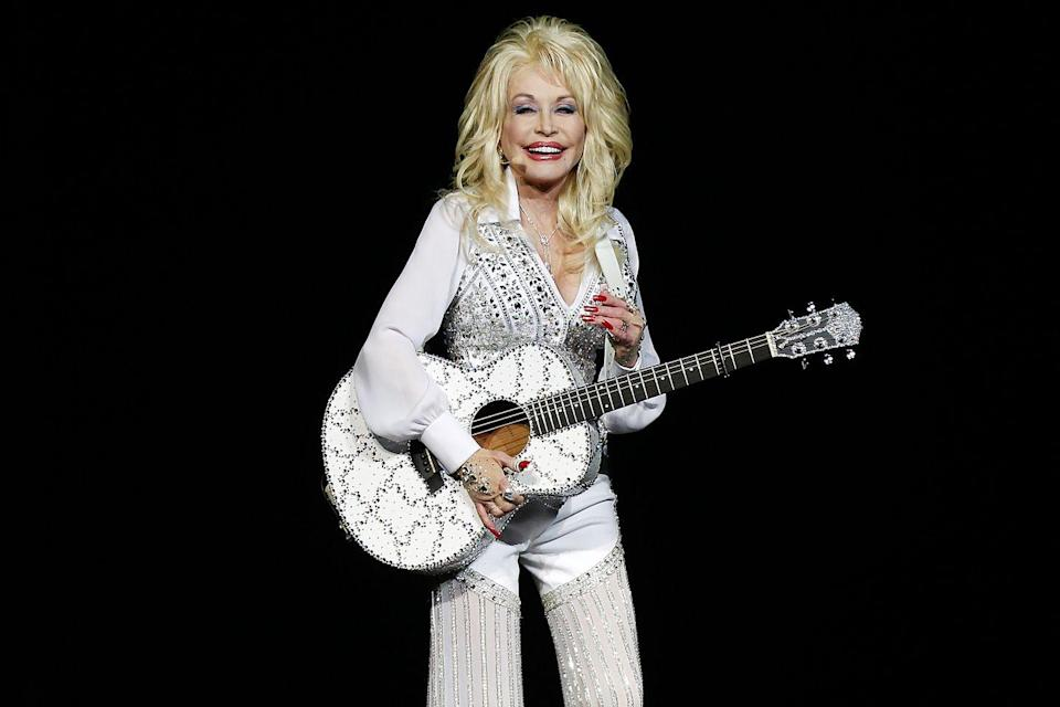 <p>Dolly Parton dazzles the crown with an all-white ensemble (and matching guitar!) in Perth, Australia. Her uniform is often a simple blouse with a beaded vest and pants for comfortable glamour.</p>