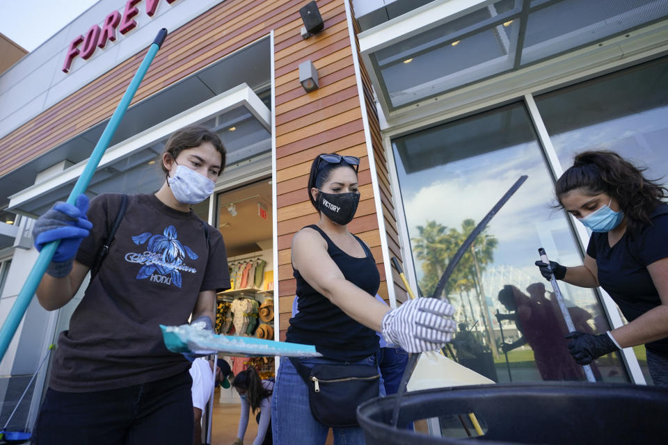 Volunteers clean up broken glass and damaged merchandise at The Pike Outlets on Monday, June 1, 2020, in Long Beach after overnight protests over the death of George Floyd . Floyd died in police custody on Memorial Day in Minneapolis. (AP Photo/Ashley Landis)