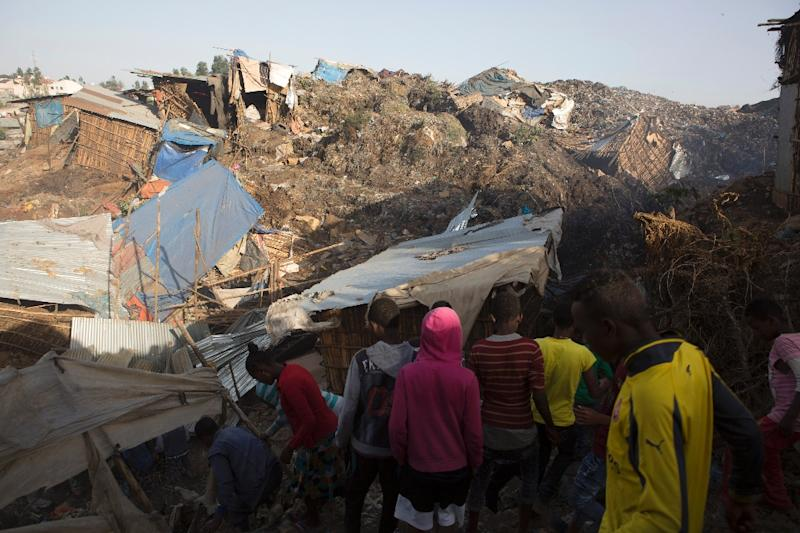 People survey the damage done to dwellings built near the main landfill of Addis Ababa on the outskirts of the city on March 12, 2017
