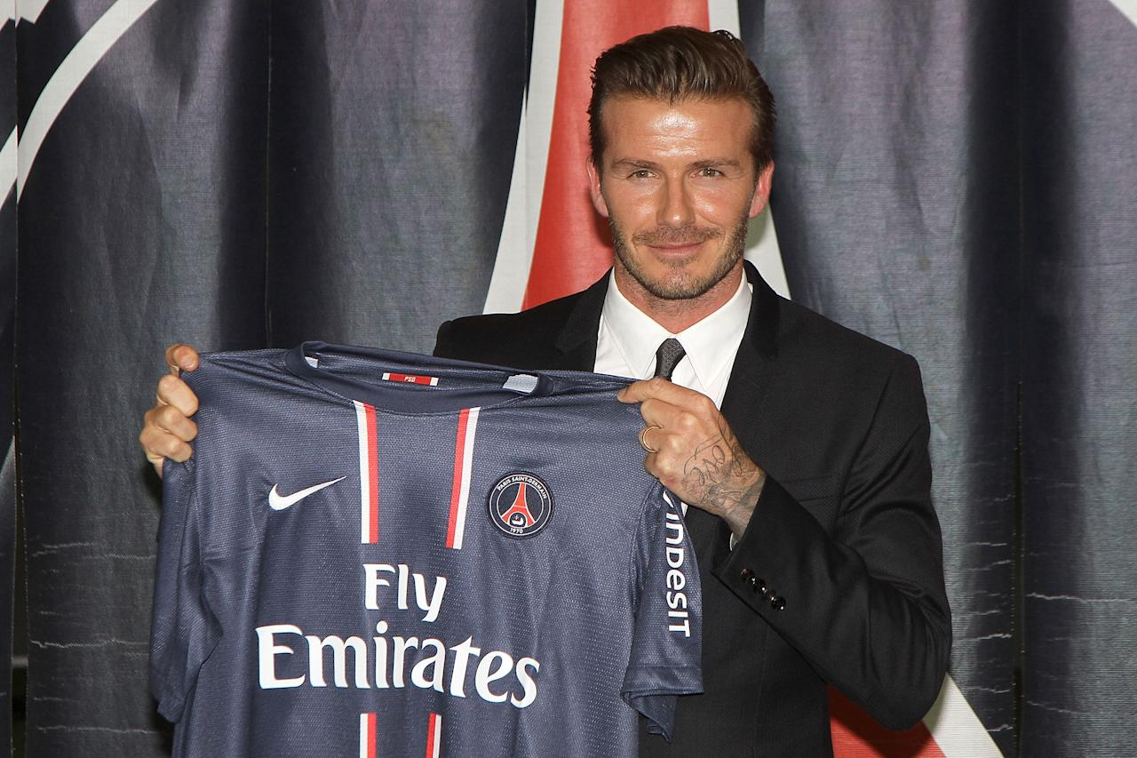 PARIS, FRANCE - JANUARY 31:  International soccer player David Beckham poses with his PSG Football shirt after his PSG signature at Parc des Princes on January 31, 2013 in Paris, France.  (Photo by Marc Piasecki/WireImage)