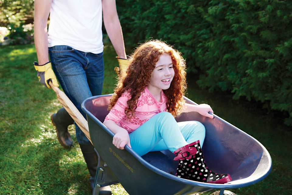 Photo of a person pushing their child in a wheelbarrow on the lawn