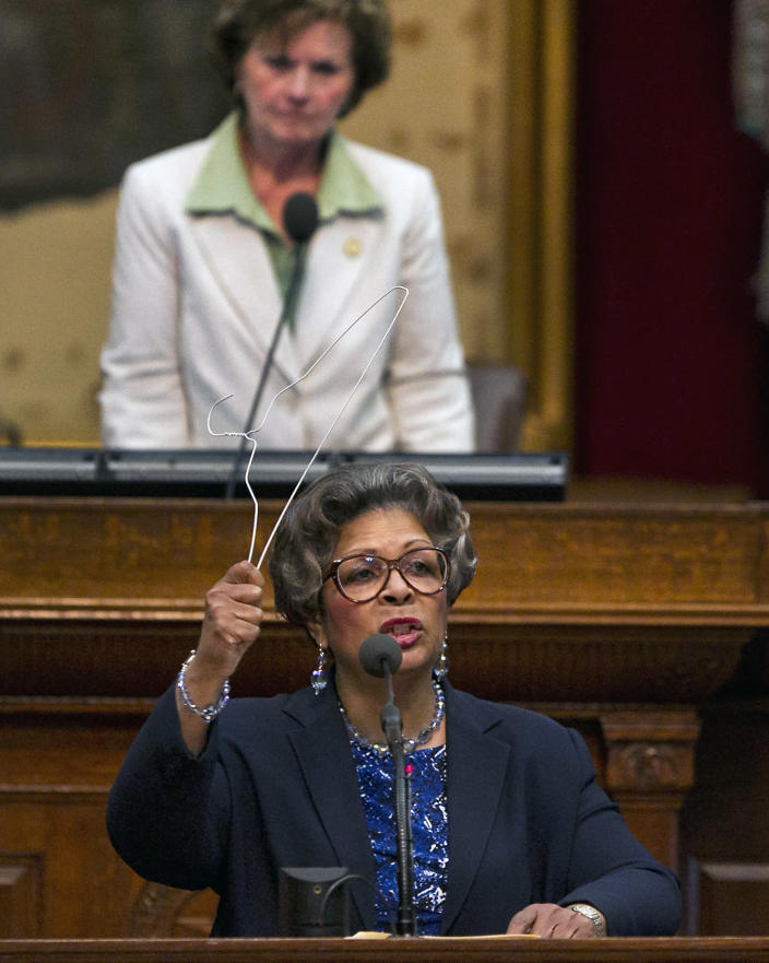 Rep. Senfronia Thompson, D-Houston, wields a hanger from podium of the House floor as she defends her attempt to add an amendment to create an exception for victims of rape and incest in Senate Bill 5 during debate on abortion at the State Capitol in Austin, Texas, on Sunday, June 23, 2013. Speaker, State Rep. Linda Harper-Brown watches from rear. If passed, the bill would ban abortions after 20 weeks, require that they take place in surgical centers, and restrict where and when women can take abortion-inducing pills_and force 37 out of 42 abortion clinics in Texas to close and undergo millions of dollars in upgrades. (AP Photo/Statesman.com, Rodolfo Gonzalez)