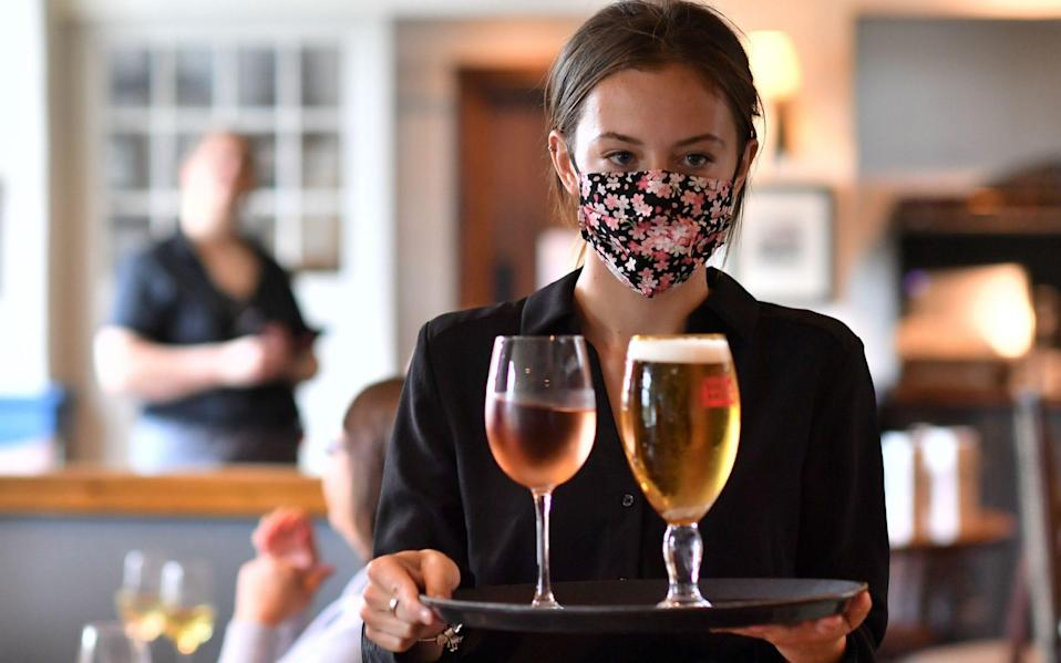 A staff member wears a face mask as she serves customers at the The Shy Horse pub and restaurant - Ben Stansall/AFP via Getty