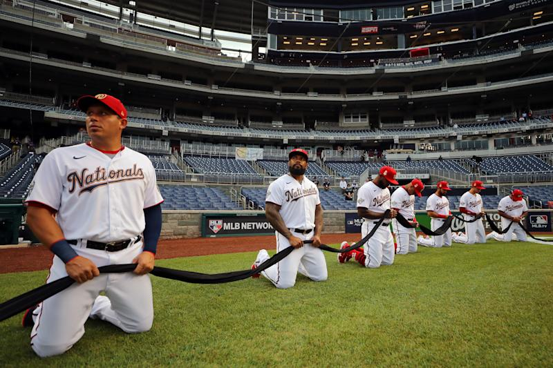 WASHINGTON, DC - JULY 23: Members of the Washington Nationals kneel and hold a black ribbon to show their support for social justice and diversity and inclusion in baseball and life during the pre-game ceremony prior to the game between the New York Yankees and the Washington Nationals at Nationals Park on Thursday, July 23, 2020 in Washington, District of Columbia. (Photo by Alex Trautwig/MLB Photos via Getty Images)