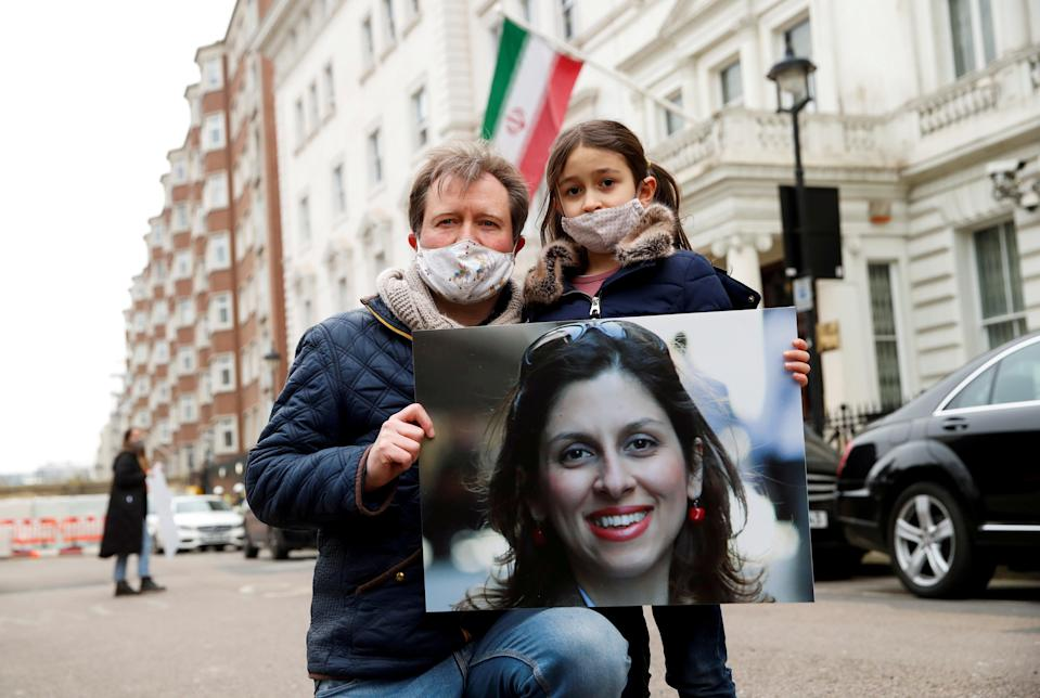 <p>Nazanin Zaghari-Ratcliffe's husband and daughter protest outside the Iranian Embassy in London</p> (REUTERS)