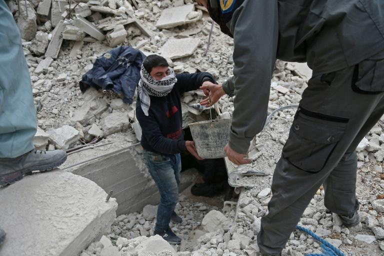 "A daily ""humanitarian pause"" announced by Russia has allowed rescuers to search for suvivors and bodies in the rubble of buildings destroyed in the bombardment of Syria's Eastern Ghouta"