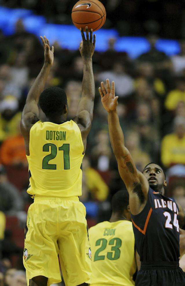 Oregon guard Damyean Dotson (21) shoots the ball over Illinois guard Rayvonte Rice (24) during the first half of an NCAA college basketball game in Portland, Or., Saturday, Dec. 14, 2013. (AP Photo/Steve Dykes)