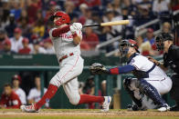 Philadelphia Phillies' Rhys Hoskins hits a two-run home run in front of Washington Nationals catcher Riley Adams and home plate umpire Mike Muchlinski in the fifth inning of a baseball game, Wednesday, Aug. 4, 2021, in Washington. (AP Photo/Patrick Semansky)