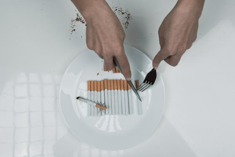 Top view close up of woman arms cutting ciggy that is lying in the plate with knife and fork