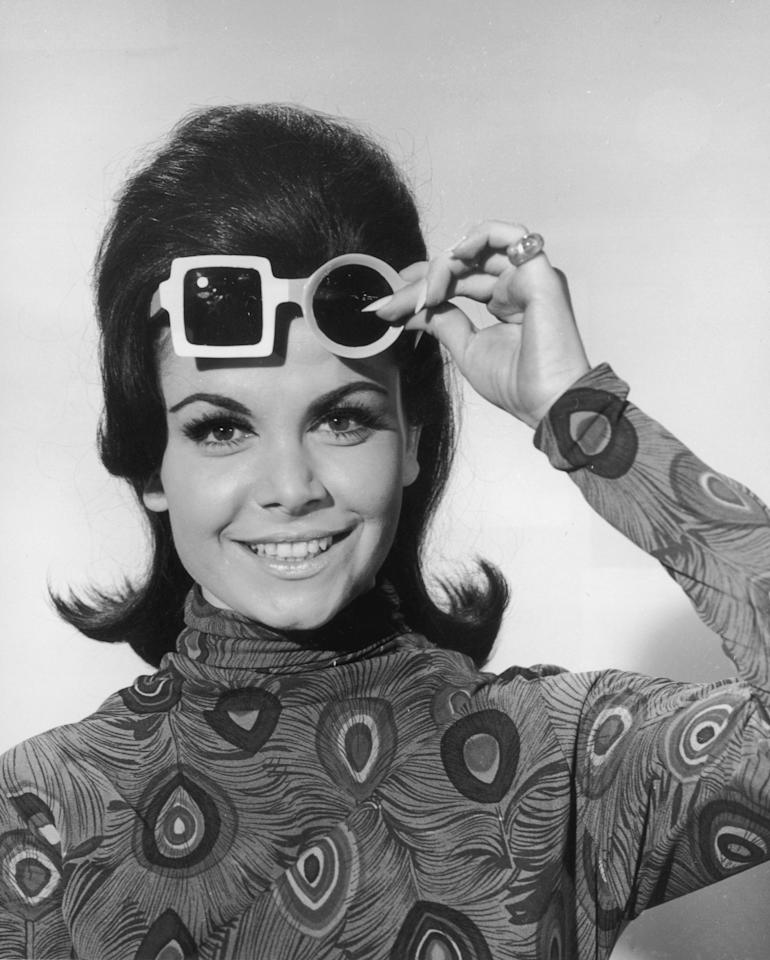 circa 1965:  Headshot portrait of American actor and singer Annette Funicello lifting up her sunglasses and smiling, 1960s. She wears a blouse with peacock plume pattern. Her sunglasses have one square and one circular lens.  (Photo by Hulton Archive/Getty Images)