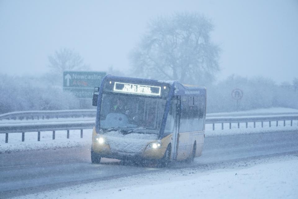 A bus that is not in service drives through snow on the A69 near Newcastle. Heavy snow and freezing rain is set to batter the UK this week, with warnings issued over potential power cuts and travel delays. (Photo by Owen Humphreys/PA Images via Getty Images)