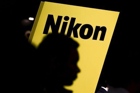 People are silhouetted against a display of the Nikon brand logo at the CP+ camera and photo trade fair in Yokohama