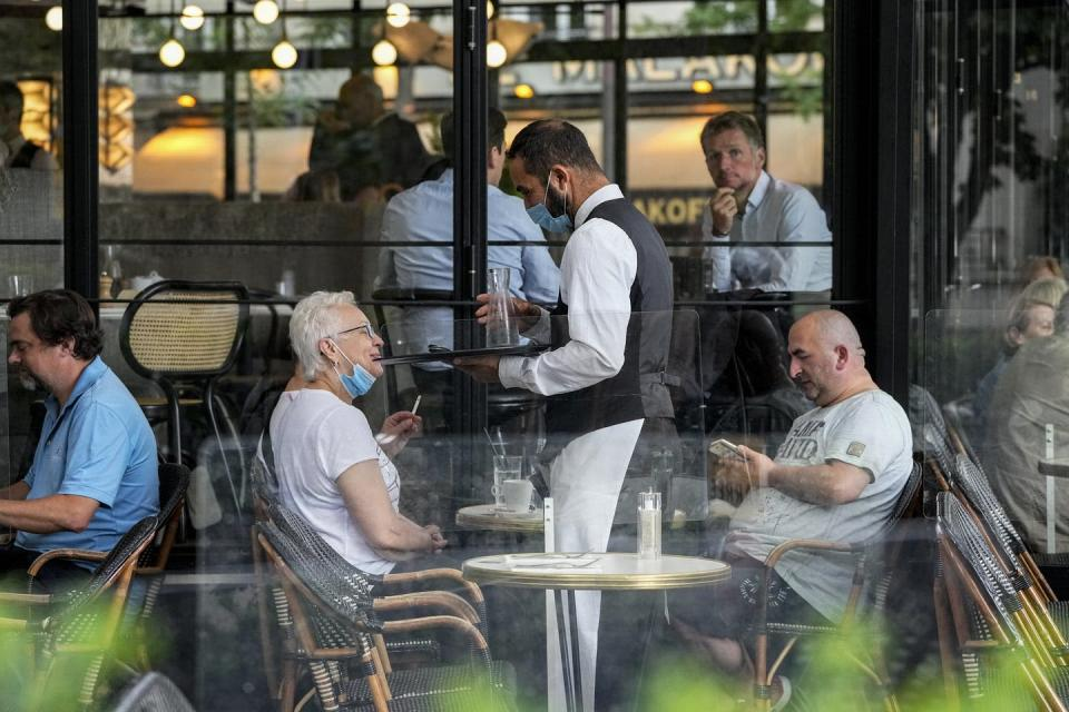 A waiter wearing a face mask to protect against coronavirus serves at a restaurant terrace in Paris