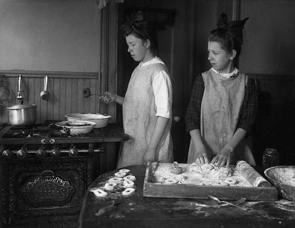 Two girls in plain smocks work side by side on the donuts