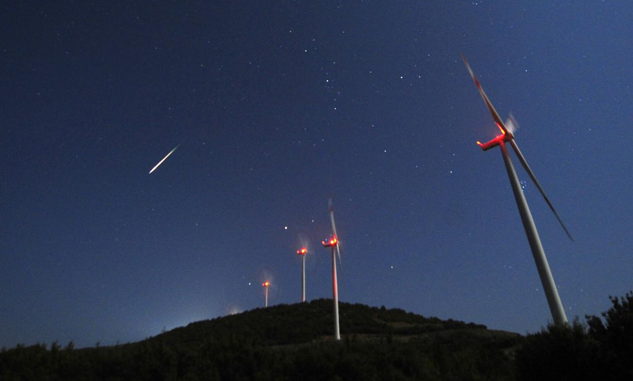 A meteor streaks across the sky during the Perseid meteor shower at a windmill farm near Bogdanci, south of Skopje, in the early morning August 13, 2014. The annual Perseid meteor shower reaches its peak on August 12 and 13 in Europe, although the lunar glare of a nearly full moon (Supermoon) makes it difficult to view the meteor shower this year, according to NASA. REUTERS/Ognen Teofilovski (MACEDONIA - Tags: ENVIRONMENT SOCIETY)