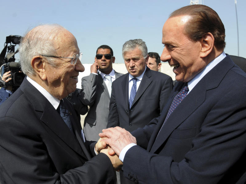 Italian Prime Minister Silvio Berlusconi, right, is welcomed by Tunisian Prime Minister Beji Caid Essebsi at Tunis airport, Monday April, 4, 2011. Berlusconi met with Tunisian leaders for tough talks aimed at halting the influx of illegal North African migrants who have been overrunning a tiny Italian island en route to mainland Europe. (AP Photo/Hassene Dridi)