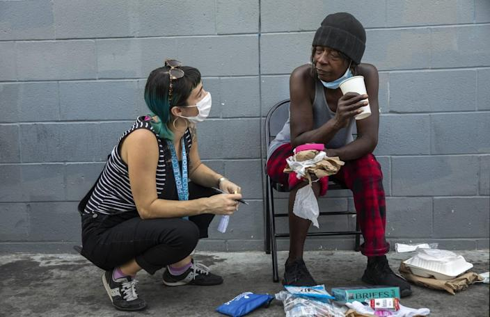 Ciara DeVozza talks with Janice Johnson as she waits for test results at a mobile clinic in downtown Los Angeles.