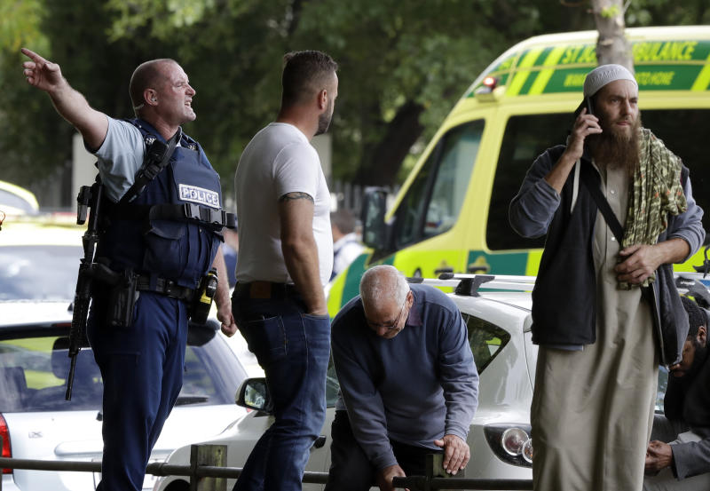 FILE - In this March 15, 2019, file photo, police attempt to clear people from outside a mosque in central Christchurch, New Zealand. New Zealand police on Wednesday, April 17, 2019 released a detailed timeline of their response to the March 15 shootings that left 50 dead at two Christchurch mosques, confirming they arrested the suspected shooter 18 minutes after receiving the first emergency call. (AP Photo/Mark Baker, File)