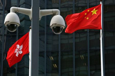 Chinese national flag and Hong Kong flag fly outside government headquarters in Hong Kong