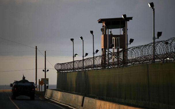 PHOTO: In this March 30, 2010 photo reviewed by the U.S. military, a U.S. trooper stands in the turret of a vehicle with a machine gun, left, as a guard looks out from a tower at the detention facility on Guantanamo Bay U.S. Naval Base in Cuba. (Brennan Linsley/AP Photo)