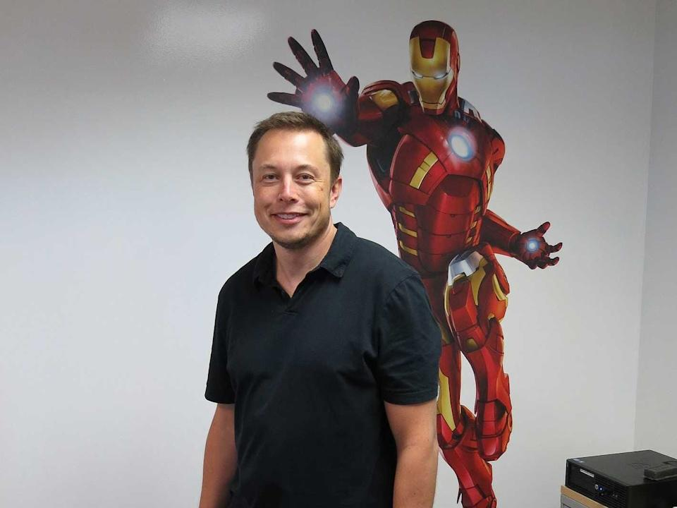 Elon Musk stands in front of a painting of Iron Man.