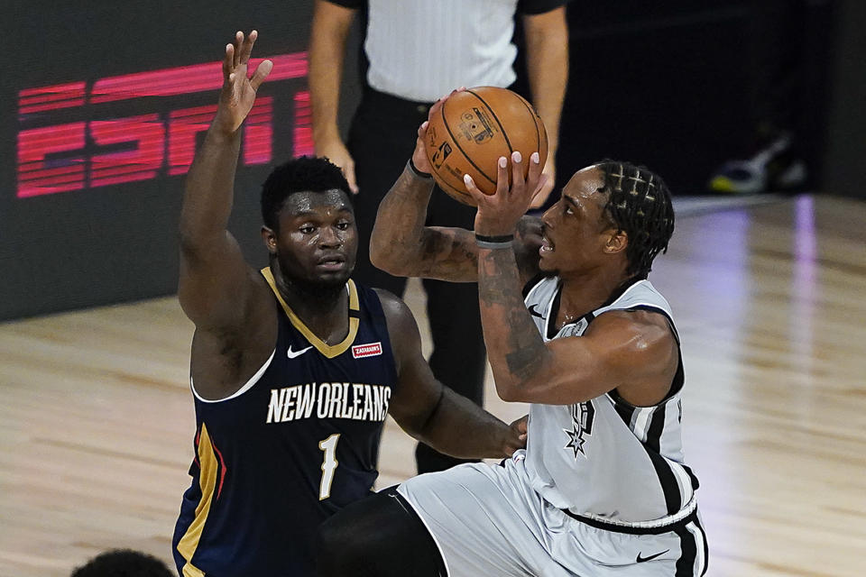 San Antonio Spurs' DeMar DeRozan, right, goes up for a shot against New Orleans Pelicans' Zion Williamson (1) during the second half of an NBA basketball game, Sunday, Aug. 9, 2020, in Lake Buena Vista, Fla. (AP Photo/Ashley Landis, Pool)