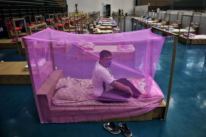 """A Bangkok Metropolitan Administration worker tests a bed for incoming COVID-19 coronavirus patients at a new field hospital in a sports stadium on the outskirts of Bangkok on April 18, 2021.<span class=""""copyright"""">Lillian Suwarnumpha—AFP/Getty Images</span>"""