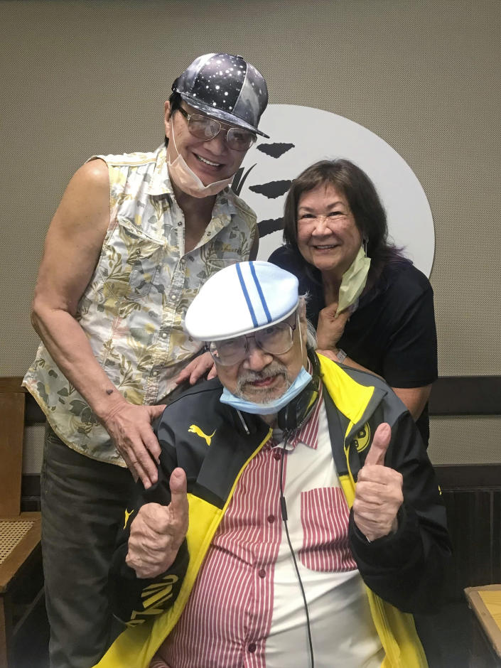 """In this photo provided by Radio Television Hong Kong (RTHK), DJ, Ray Cordeiro, also known as Uncle Ray, center, poses with Hong Kong singer Sam Hui, left, and his wife Rebecca at the studio in RTHK, the broadcaster in Hong Kong on Feb. 14, 2021. After more than seven decades in radio, the 96-year-old Hong Kong DJ bid farewell to his listeners Saturday, May 15, 2021 with """"Time to Say Goodbye,"""" sung by Sarah Brightman and Andrea Bocelli. (Radio Television Hong Kong via AP)"""