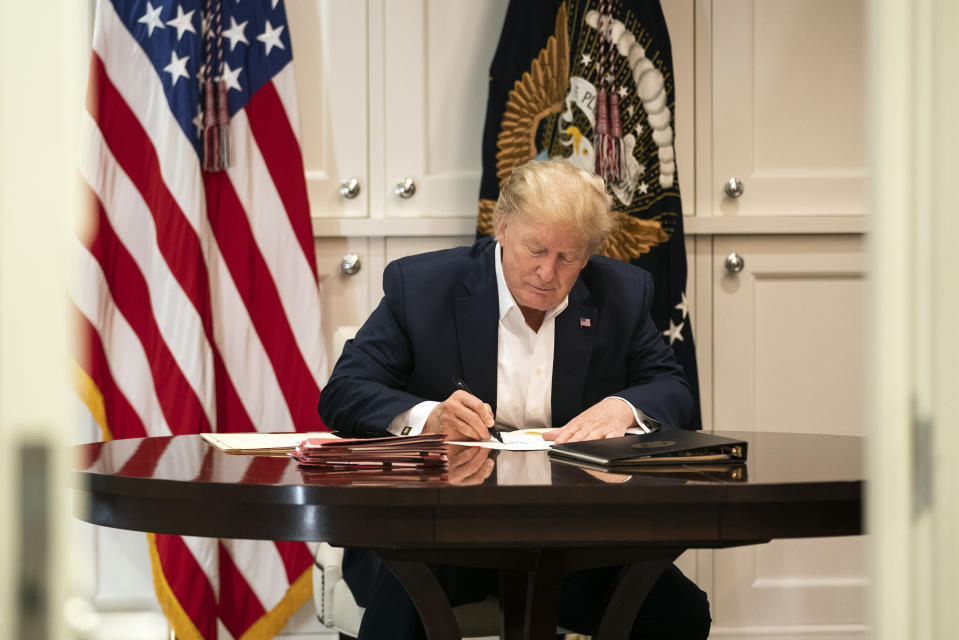 In this image released by the White House, President Donald Trump works in the Presidential Suite at Walter Reed National Military Medical Center in Bethesda, Md. Saturday, Oct. 3, 2020, after testing positive for COVID-19. (Joyce N. Boghosian/The White House via AP)