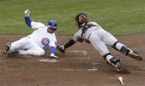 Chicago Cubs' Welington Castillo, left, scores on a single hit by Brent Lillibridge as San Francisco Giants catcher Buster Posey, right, dives in with the late tag during the third inning of a baseball game in Chicago, Thursday, April 11, 2013. (AP Photo/Nam Y. Huh)