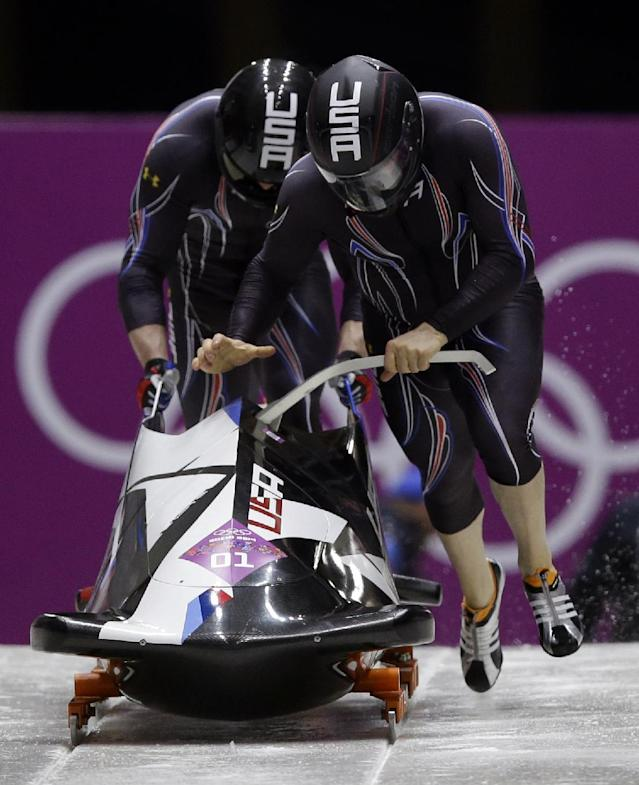 The team from the United States USA-1, piloted by Steven Holcomb and brakeman Steven Langton, start their first run during the men's two-man bobsled competition at the 2014 Winter Olympics, Sunday, Feb. 16, 2014, in Krasnaya Polyana, Russia. (AP Photo/Dita Alangkara)